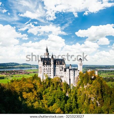 Beautiful view Neuschwanstein Castle (Bavaria, Germany) during early autumn, with blue sky and white clouds - stock photo