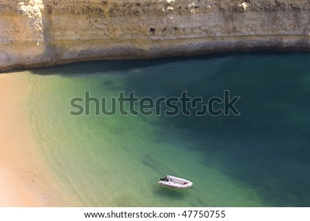 Beautiful view of an idyllic wild beach in summertime with boat- sand and sea at Algarve, Portugal coast. - stock photo