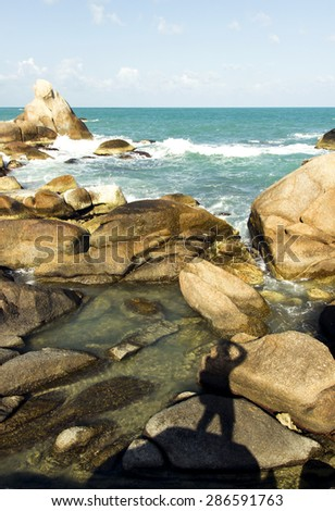 beautiful view of coastline rocks, sea waves and photographer silhouette. summer tour adventure - stock photo