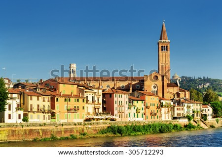 Beautiful view of colorful facades of old houses on waterfront of the Adige River in Verona, Italy. The Santa Anastasia church on blue sky background. Verona is a popular tourist destination of Europe - stock photo