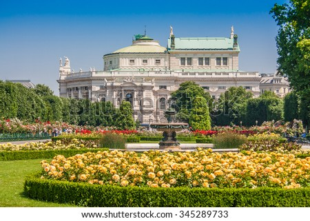 Beautiful view of famous Volksgarten (People's Garden) public park with historic Burgtheater in the background on a sunny day with blue sky in summer, Innere Stadt first district of Vienna, Austria - stock photo