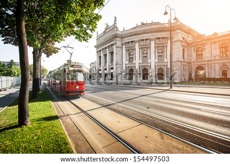 Beautiful view of famous Wiener Ringstrasse with historic Burgtheater (Imperial Court Theatre) and traditional red electric tram at sunset in Vienna, Austria - stock photo
