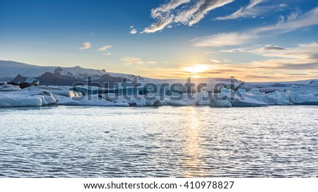 Beautiful view of icebergs in Jokulsarlon glacier lagoon at sunset, Iceland, selective focus, global warming and climate change concept - stock photo