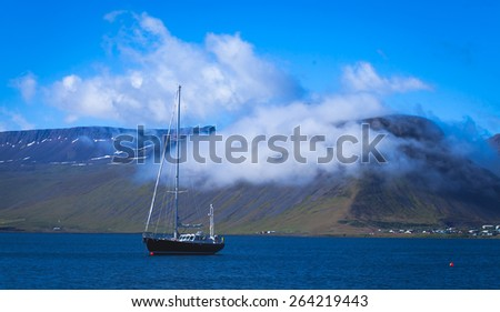 Beautiful view of icelandic fjord and city in iceland with red houses, ships and yachts - stock photo