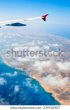 Beautiful view of island Cyprus and Mediterranean sea from the airplane window. Light clouds from above. - stock photo