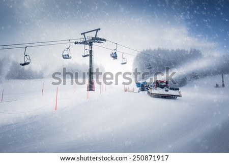 Beautiful view of long ski lift line and the working snow cannon on Austrian Alps - stock photo