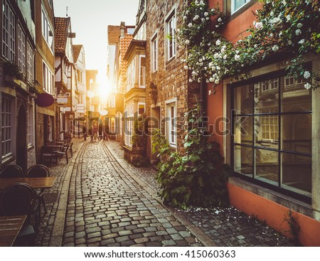 Beautiful view of old town in Europe in beautiful golden evening light at sunset in summer with pastel toned retro vintage Instagram style grunge filter and lens flare sunlight effect - stock photo