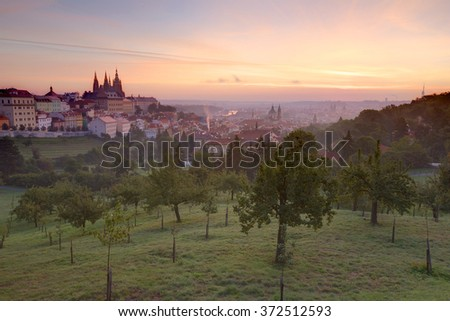Beautiful view of Prague on a misty morning with rosy sunrise sky ~ Panorama of Prague Old Town with majestic Prague Castle & St. Vitus Cathedral on the left and a golden rising sun in the background - stock photo