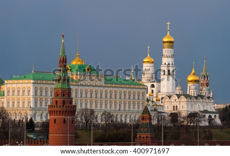 Beautiful view of red brick Moscow kremlin tower with golden church 's domes and the state kremlin palace in the evening  or sunset of middle spring. Capital of Russia - stock photo