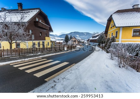Beautiful view of road going through small town in Austrian Alps - stock photo