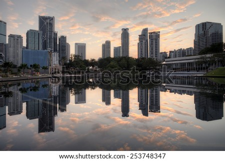 Beautiful view of symphony lake klcc with reflections during sunrise (soft focus, shallow DOF, slight motion blur) - stock photo