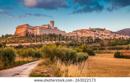 Beautiful view of the ancient town of Assisi with dramatic cloudscape in golden evening light, Umbria, Italy - stock photo