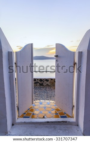 Beautiful view of the Caldera through the open wooden door at sunset.Santorini (Thira) island.Cyclades.Greece.Europe - stock photo