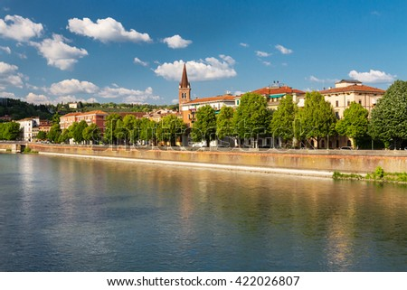 Beautiful view of the colorful facades of old houses with trees on waterfront of the Adige River in Verona, Italy - stock photo