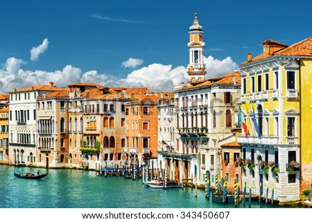 Beautiful view of the Grand Canal with gondola and colorful facades of old medieval houses from the Rialto Bridge in Venice, Italy. Venice is a popular tourist destination of Europe. - stock photo