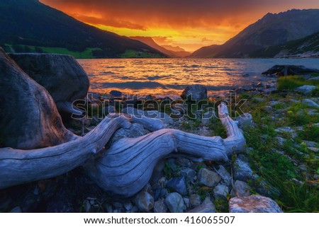 Beautiful view of the lake Resia. Dramatic sky and colorful sunset. Alps, Italy, Europe. - stock photo