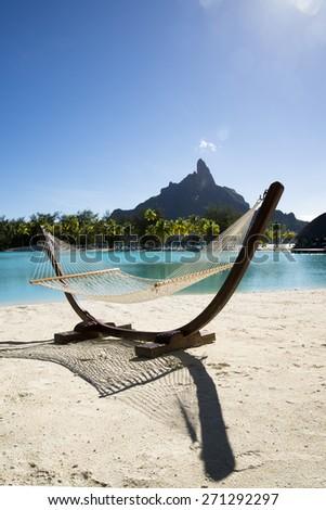Beautiful view of the Otemanu mountain , looking towards through hammock standing on the white sand, turquoise lagoon and palms, Bora Bora , French Polynesia - stock photo