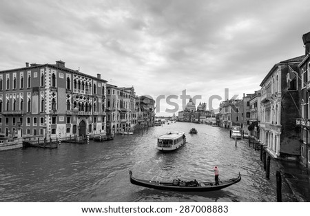 Beautiful view of traditional Gondola and boats on Canal Grande with Basilica di Santa Maria della Salute church in background at a cloudy day, Venice (Venezia), Italy, Europe, black and white - stock photo