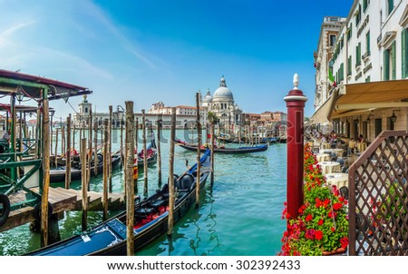 Beautiful view of traditional Gondolas on Canal Grande with historic Basilica di Santa Maria della Salute in the background on a sunny day in Venice, Italy - stock photo