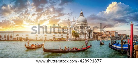 Beautiful view of traditional Gondolas on famous Canal Grande with historic Basilica di Santa Maria della Salute in the background in romantic golden evening light at sunset in Venice, Italy - stock photo