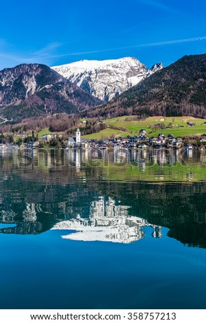 Beautiful View Of Wolfgang Lake With St. Wolfgang Im Salzkammergut And Grosser Hollkogel In The Background And Their Reflection On The Water-Salzkammergut, Austria,Europe - stock photo