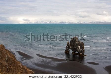Beautiful view on Hvitserkur rock, sea and black sand beach on the northern coast of Iceland. Legends say it is a petrified troll. - stock photo