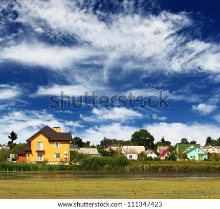 Beautiful view on Ukrainian village by the river over blue cloudy sky - stock photo