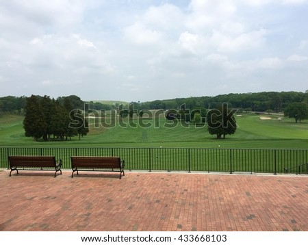 Beautiful view overlooking the tee box and fairway of a wide open green golf course. - stock photo