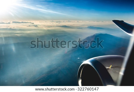 Beautiful view through airplane window, airplane flying above the clouds and mountains. Sunrise and beautiful sun flare. - stock photo