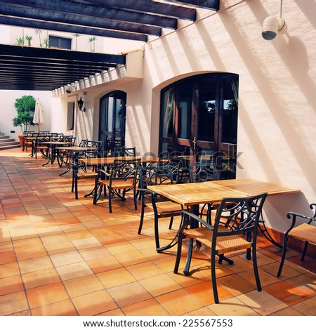 Beautiful view with tables and chairs at a open terrace cafe in mediterranean town (Portugal). Square toned image, instagram effect - stock photo
