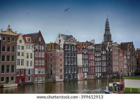 Beautiful views of the ancient buildings at the waterside and view of Oude Kerk (Old Church) from Damrak canal in Amsterdam, the Netherlands - stock photo