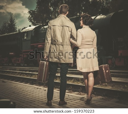 Beautiful vintage style couple with suitcases on  train station platform - stock photo