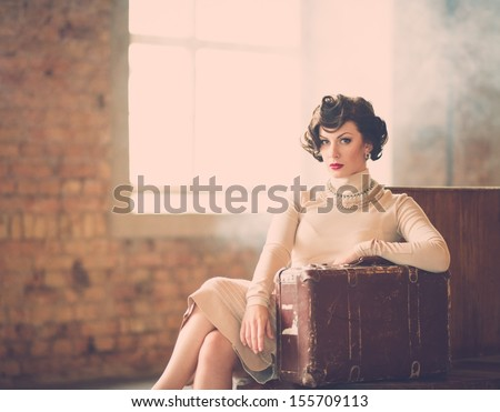 Beautiful vintage style young woman with suitcase on a train station - stock photo