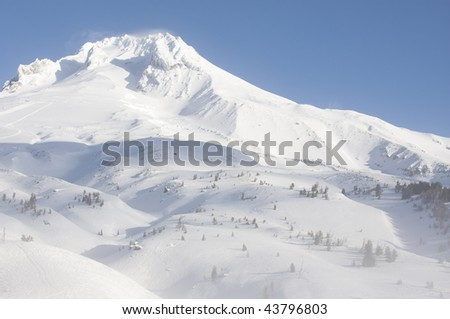 Beautiful Vista of Mount Hood in the Pacific Northwest with Blue Skies and the wind blowing through the snow. - stock photo