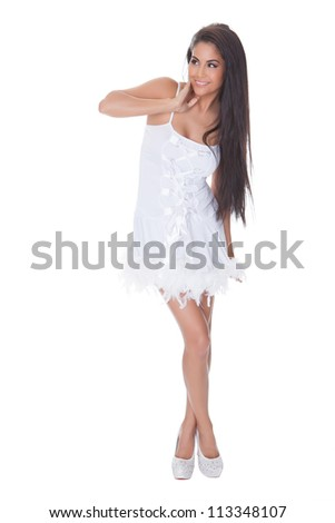 Beautiful vivacious woman with a lovely smile posing in a stylish short white cocktail dress trimmed with feathers and wearing stilettos - stock photo