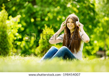 Beautiful vivacious young woman listening to music as she sits on the grass in a wooded leafy park smiling with pleasure , copyspace to the left - stock photo