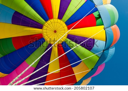 Beautiful vivid and vibrant colors of a hot air balloon. Exciting flying experience in the blue sky. - stock photo