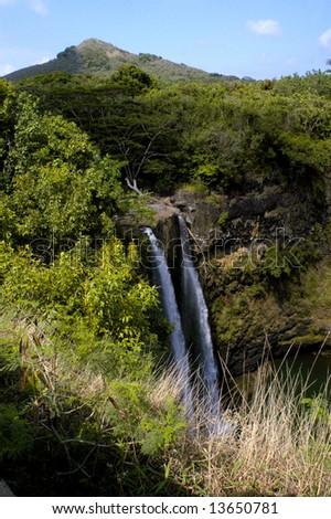 Beautiful Wailua Falls on Kauai, Hawaii has its own unique twin falling streams.  Mountains in background and blue sky. - stock photo