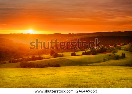 Beautiful warm spring image of a morning sunrise over fields, meadows and forests - stock photo