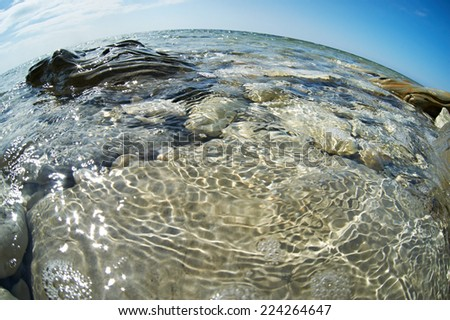 Beautiful water surface on a rocky seashore in sunny day - stock photo