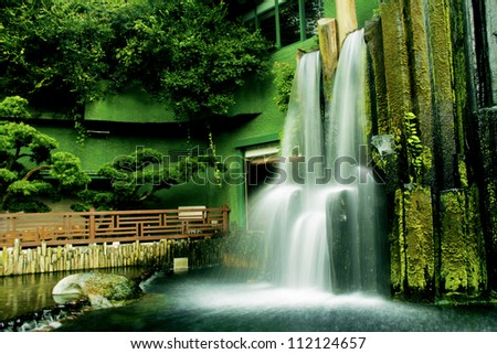 Beautiful waterfall in Chinese Classical Garden called Nan Lian in Hong Kong situated on the Kowloon Island. Blurred motion. - stock photo