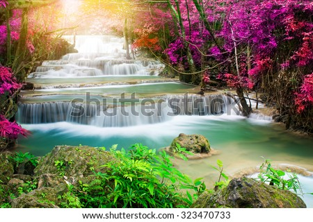Beautiful waterfall in colorful autumn forest with sun light  - stock photo