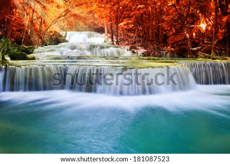beautiful waterfall in deep autumn forest - stock photo