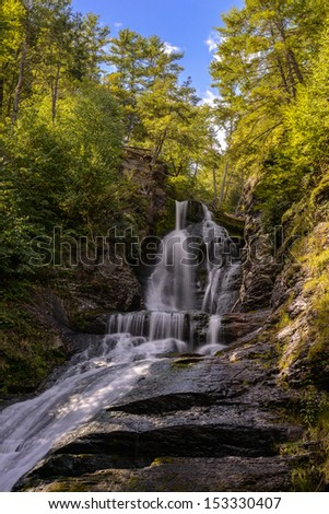 beautiful waterfall in forest, autumn landscape scenery - stock photo