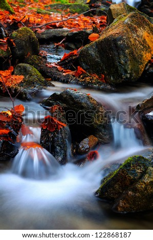 Beautiful waterfall of the little river in great Romanian forest, after the autumn rains - stock photo