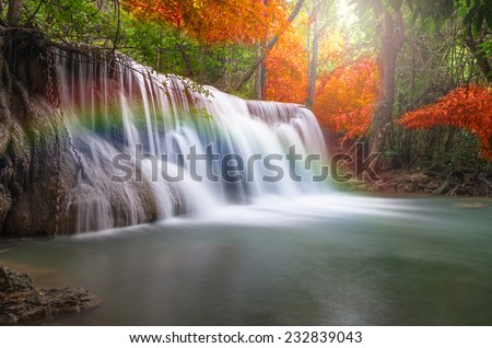 Beautiful waterfall with rainbow in the forest - stock photo