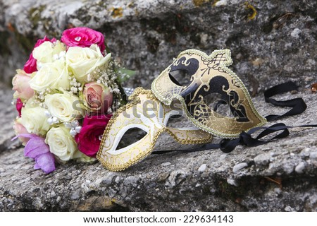 Beautiful wedding bouquet and Venice mask at stone steps  - stock photo