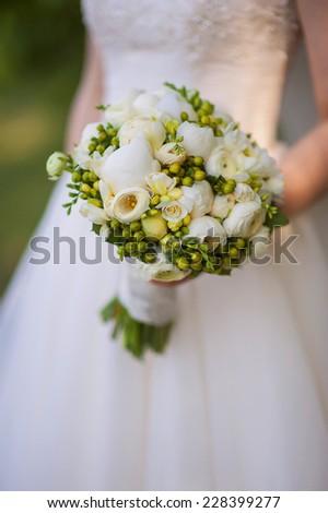 Beautiful wedding bouquet in bride's hand. - stock photo