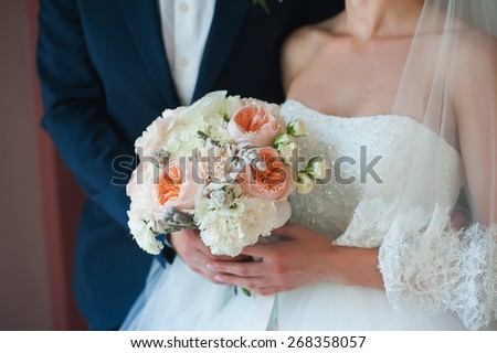Beautiful wedding bouquet in hands of the bride and groom - stock photo