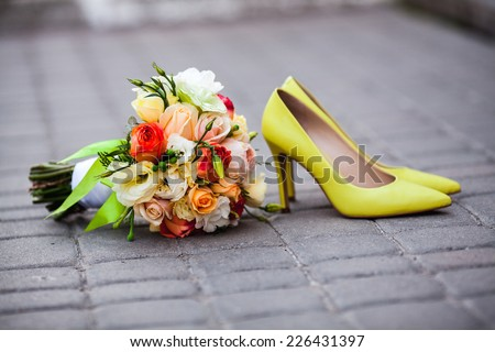 Beautiful wedding bouquet of roses and peonies on the pavement. Stylish and fashionable shoes bride yellow. Lemon yellow wedding. belt tiles. delicate flowers - stock photo